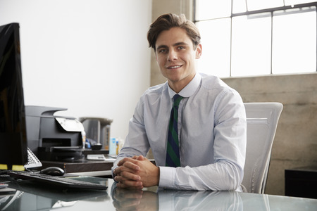 Young white businessman at an office desk, smiling to camera Stock Photo