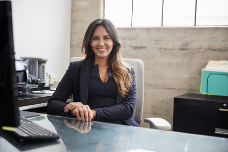 Mixed race woman with long hair sitting at desk in office