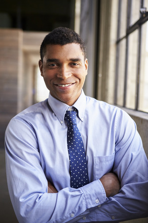 Smiling mixed race businessman with arms crossed, portrait Stock Photo