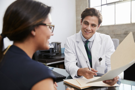 White male doctor showing file to female patient in office