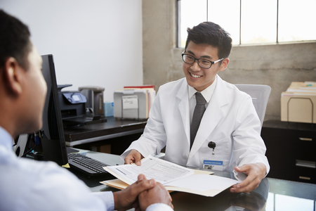 Happy Asian male doctor in consultation with male patient Stock Photo
