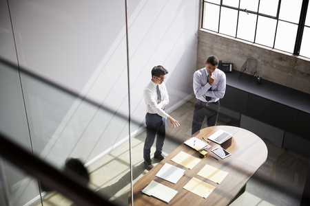 Two businessmen talk standing in an office, elevated view