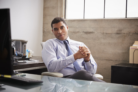Mixed race businessman at an office desk looking to camera
