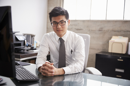 Young Asian businessman at an office desk, looking to camera