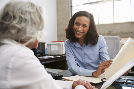 Smiling female analyst in consultation with senior woman