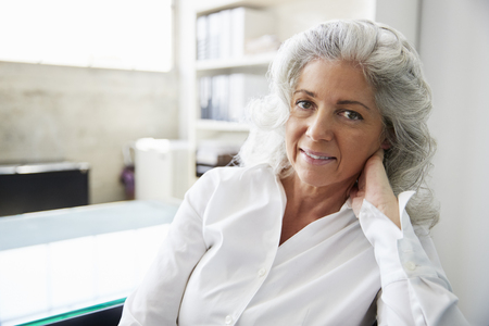 Professional senior white woman in office looking to camera