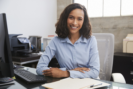 Young female professional at desk smiling to camera Stockfoto