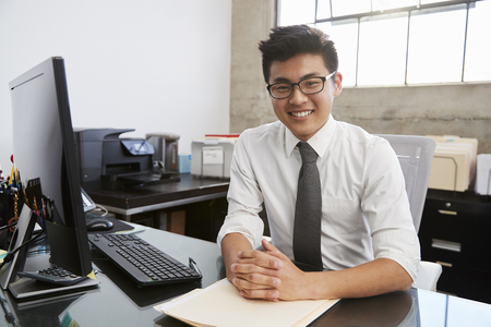 Young Asian male professional at desk smiling to camera Banco de Imagens