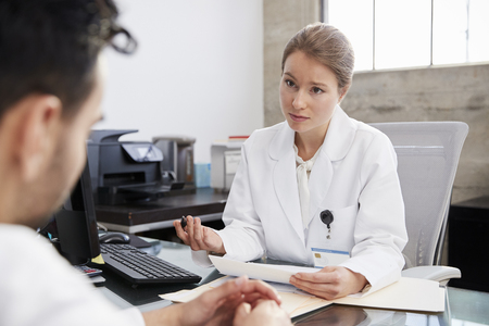 Concerned female doctor in consultation with male patient