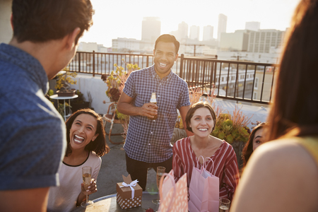 Portrait Of Friends Gathered On Rooftop Terrace To Celebrate Birthday With City Skyline In Background