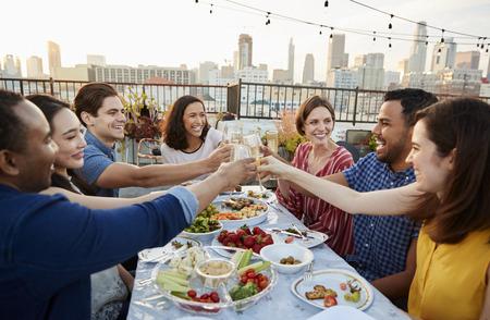 Amigos reunidos en la terraza de la azotea para comer con el horizonte de la ciudad en segundo plano. Foto de archivo