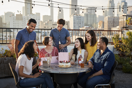 Friends Gathered On Rooftop Terrace To Celebrate Birthday With City Skyline In Background