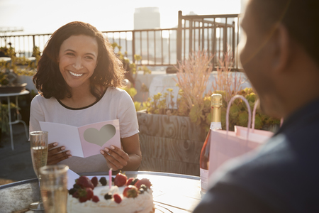 Man Giving Woman Gift And Card As They Celebrate On Rooftop Terrace With City Skyline In Background Stock Photo