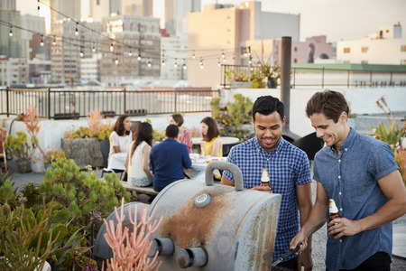Friends Gathered On Rooftop Terrace For Barbecue With City Skyline In Background Stock Photo