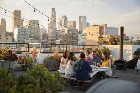 Vrienden verzamelden zich op het dakterras voor een maaltijd met de skyline van de stad op de achtergrond