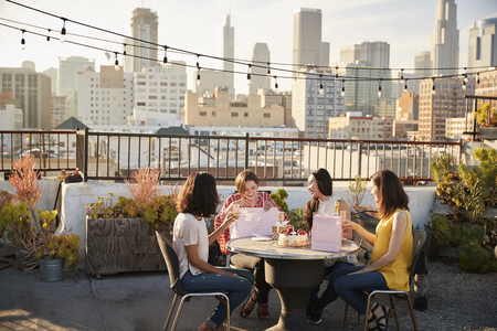 Female Friends Celebrating Birthday On Rooftop Terrace With City Skyline In Background Stock Photo