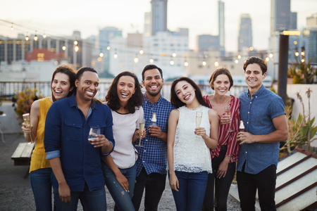 Portrait Of Friends Gathered On Rooftop Terrace For Party With City Skyline In Background Making Toast With Drinks