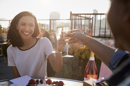 Couple Making Toast To Celebrate Birthday On Rooftop Terrace With City Skyline In Background Stock Photo