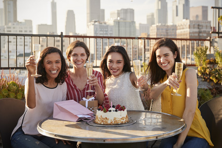 Portrait Of Female Friends Making Toast To Celebrate Birthday On Rooftop Terrace With City Skyline In Background