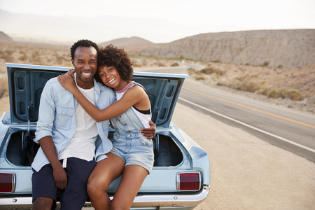 Portrait Of Couple Sitting In Trunk Of Classic Car On Road Trip Stock Photo