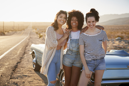 Portrait Of Female Friends Enjoying Road Trip Standing Next To Classic Car On Desert Highway Stock Photo