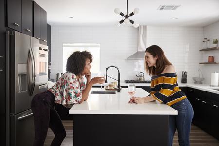 Deux amies buvant du vin à la maison debout près de l'île de cuisine