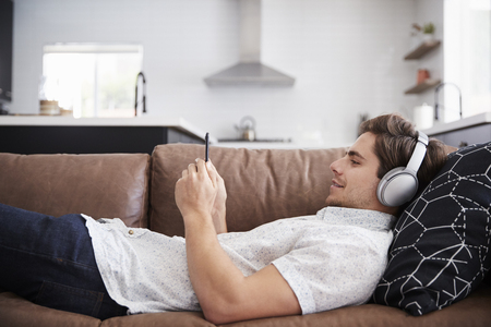 Man Wearing Wireless Headphones Lying On Sofa At Home Streaming From Mobile Phone