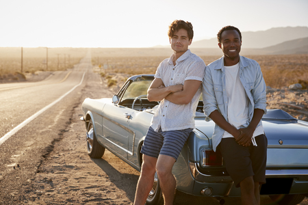 Portrait Of Two Male Friends Enjoying Road Trip Standing Next To Classic Car On Desert Highway
