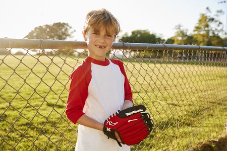 A boy holding baseball mitt and smiling to camera