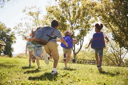 Five school kids running in a field, back view, close up