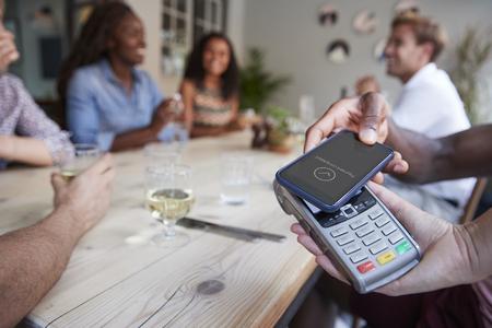 Primo piano del cliente nel ristorante che paga il conto con l'app telefono contactless
