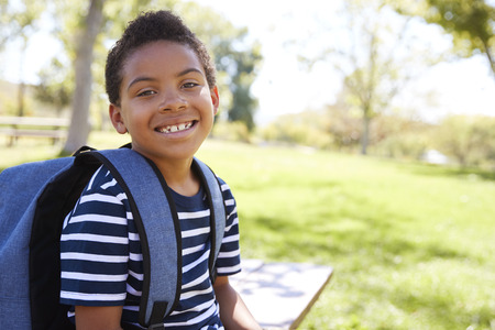Young mixed race schoolboy with backpack smiles to camera Stock Photo