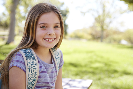 Young smiling schoolgirl looking to camera, portrait Banco de Imagens