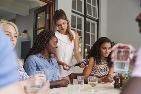 Female Customer In Restaurant Paying Bill Using Contactless Credit Card Terminal Stockfoto