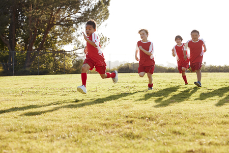 Four young boys in football strip running in a playing field 스톡 콘텐츠