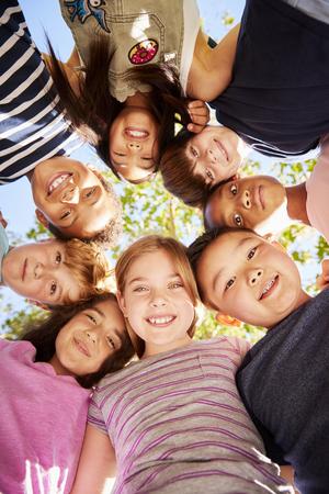 Groep kinderen buiten kijken neer op camera, verticaal Stockfoto