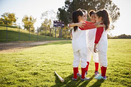 Équipe de baseball d'écolière parlant en équipe avant le match