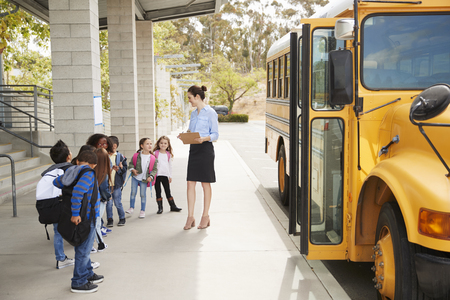 Teacher talks to young school kids by school bus, side view Banque d'images
