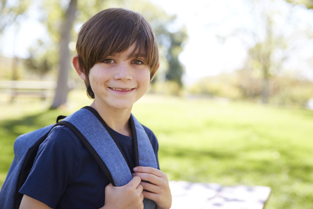Young schoolboy looks to camera and smiles, portrait