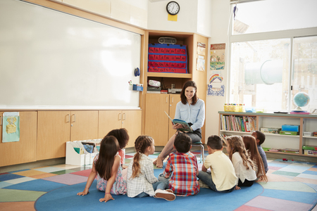 School kids sitting on the floor gathered around teacher Stock Photo