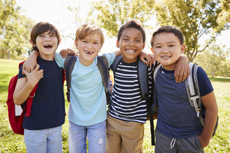 Czterech młodych uśmiechniętych uczniów spędzających czas na wycieczce szkolnej