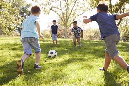 Four young schoolboys playing football together in the park Stockfoto - 109006406