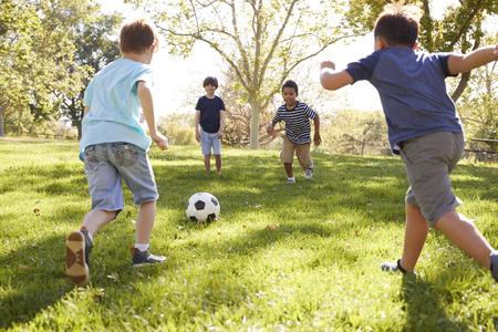 Vier jonge schooljongens voetballen samen in het park
