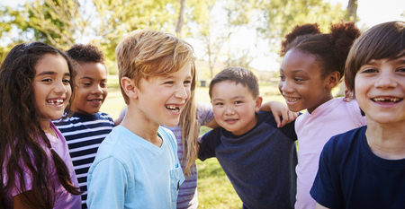 Multi-ethnic group of schoolchildren laughing, outdoors Banco de Imagens