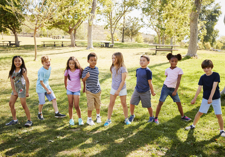 Multi-ethnic group of schoolchildren playing in park Stock Photo