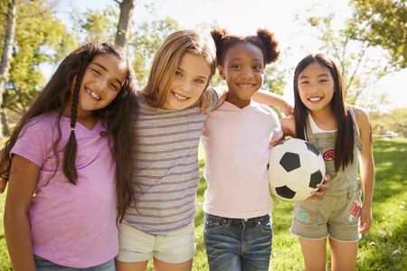Four young schoolgirls holding football embrace each other Banco de Imagens