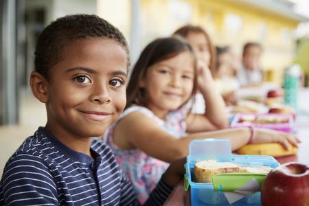 Jonge jongen en meisje die op de tafel van de schoollunch naar camera glimlachen