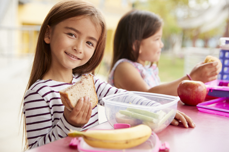 Elementary school girls eating at school lunch table