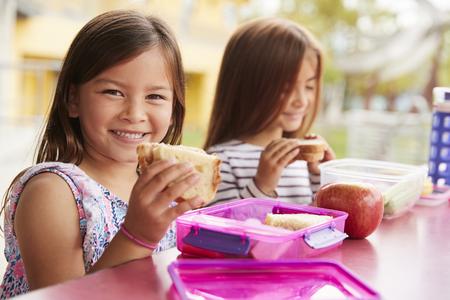 Jonge schoolmeisjes die broodjes houden aan de tafel van de schoollunch Stockfoto - 109005766