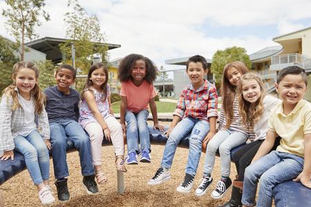 Elementary school kids sitting on carousel in the schoolyard Banco de Imagens